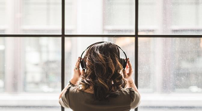 Jeune femme de dos avec un casque de musique sur la tête