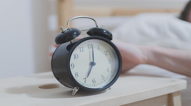 Homme arrêtant un réveil