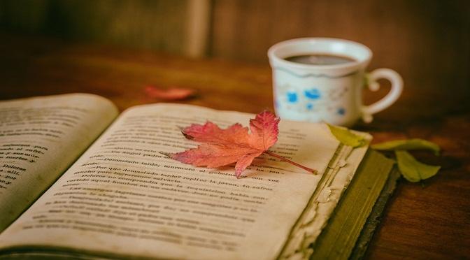 Livre ouvert devant une tasse de café