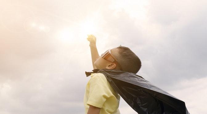 Petit garçon tendant le bras vers le ciel