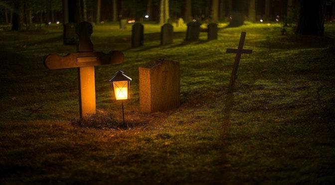 Tombe éclairée avec une lanterne dans un cimetière