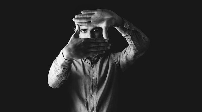 Homme regardant dans un cadre fait avec ses mains