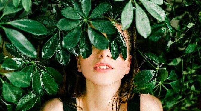 Femme cachée derrière une plante